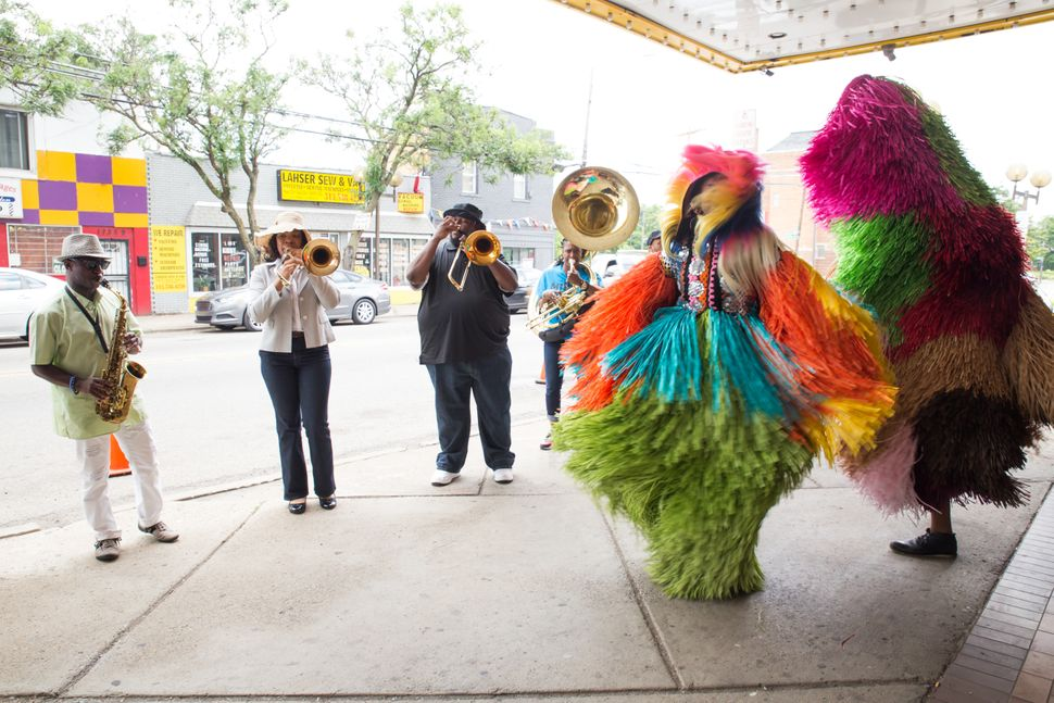 The Gabriel Brass Band performing with dancers from Sidewalk Detroit in Cave's Soundsuits