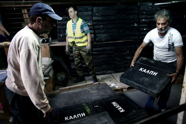 Municipal workers carry ballot boxes into a warehouse in Athens, Greece, on July 2, 2015, in preparation for the upcoming ref