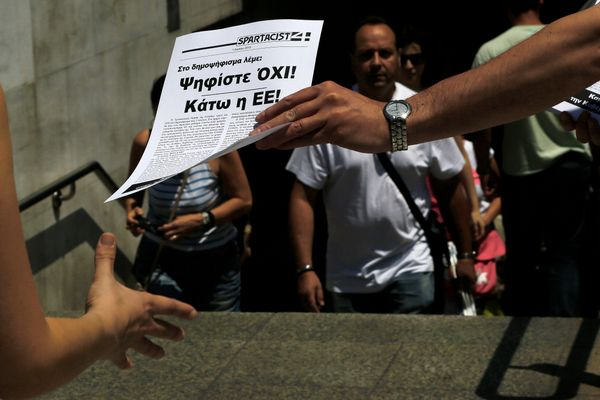 "A man passes out a leaflet reading in Greek ""Vote NO in the referendum, Down with the EU"" in Athens, Greece, on July 2, 2015"