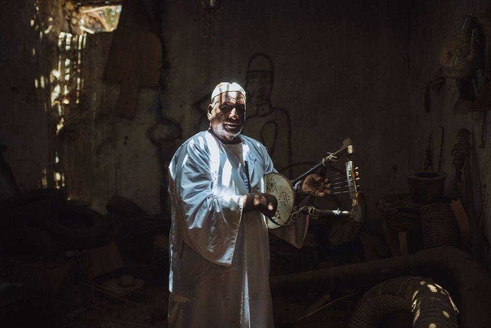 """Hajj Eissa plays on his old tambour in his """"room of memories"""" in Toshka Village, the immigration area in Kom Umbo. Hajj Eissa"""