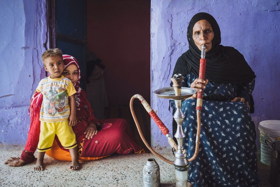 Hajja Sameeha smokes shisha in her home in Nag' Besion, her daughter Mona and grandson Yaseen are sitting with her. These old
