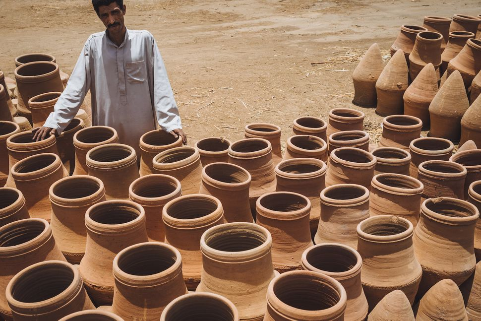 """Hassan selling pottery in Balana, near Kom Umbo. The large pots are called """"€œolla"""" and are used to store water and maintain"""