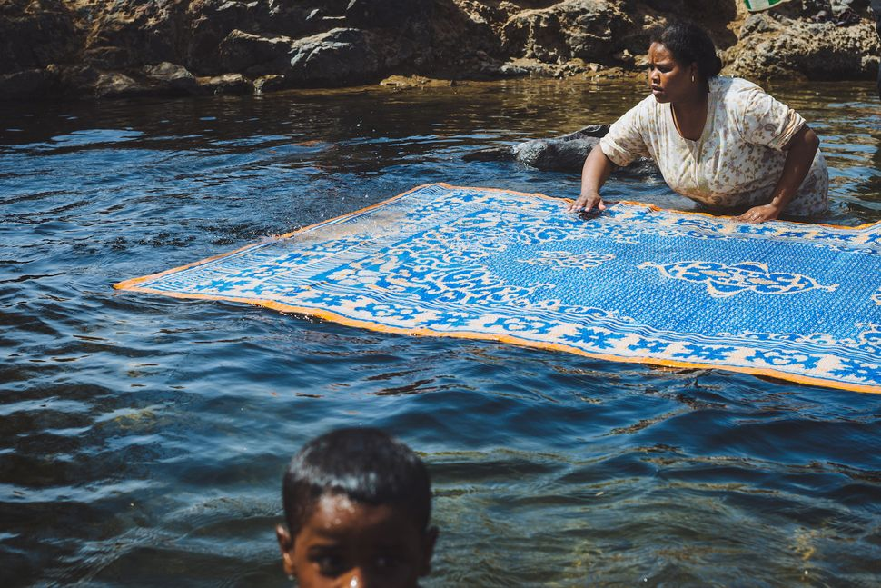 A Nubian woman cleaning her carpet in the Nile while her child is having a swim. Cleanliness is a well-known quality of the N