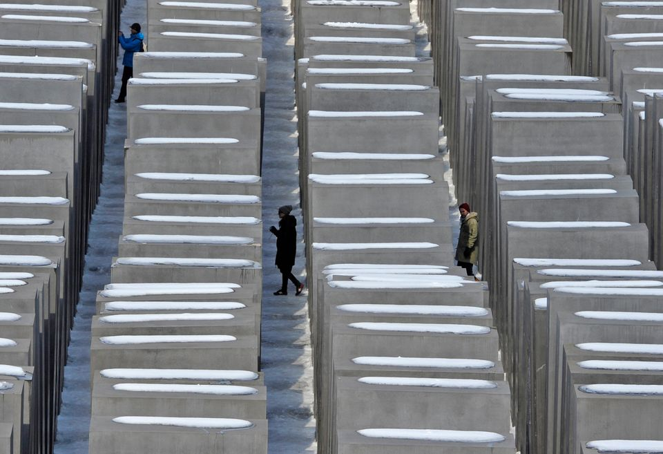 Persons walk through the holocaust memorial in Berlin, on a sunny but cold Monday March 25, 2013. (AP Photo/dpa, Markus Heine