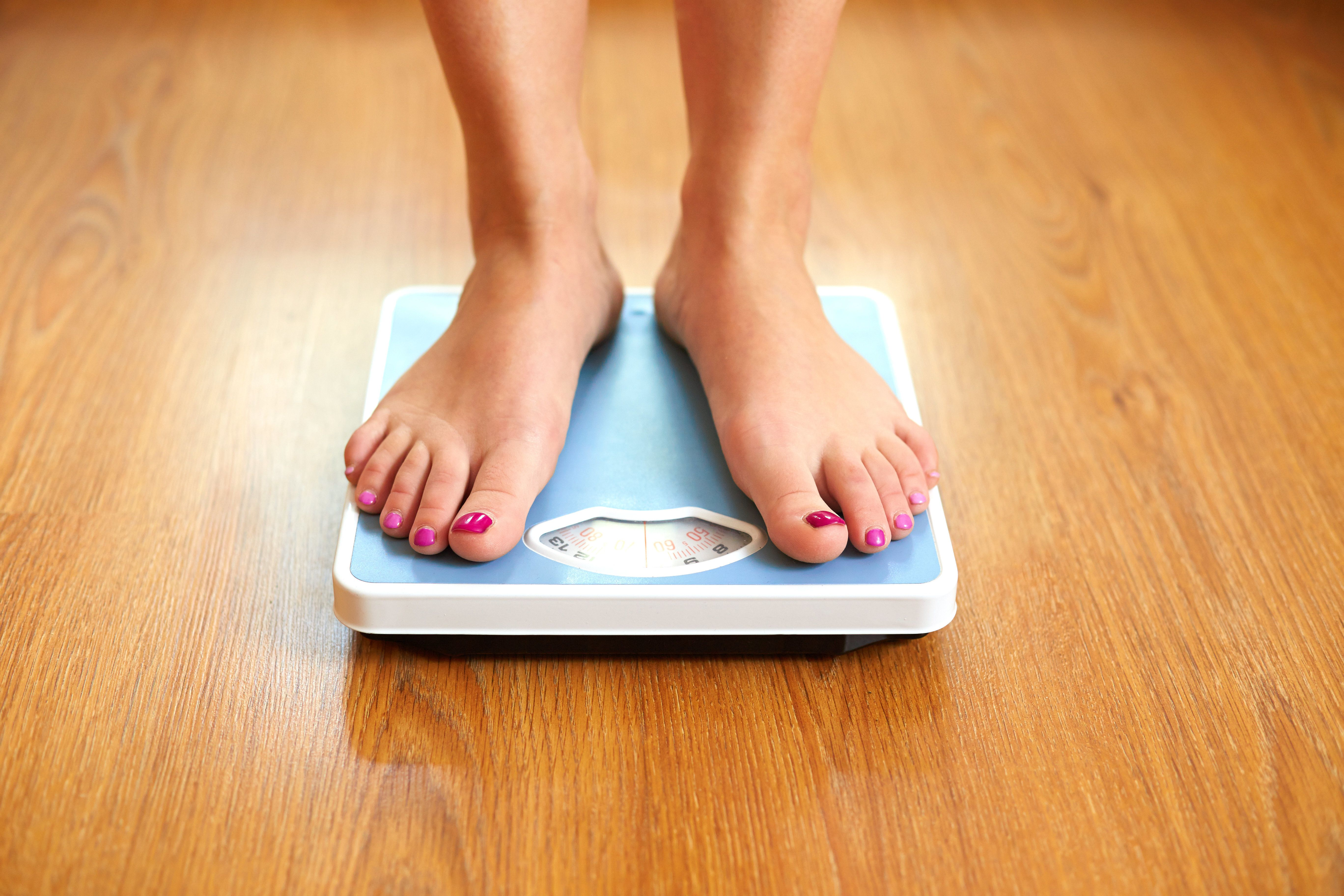 Female bare feet with weight scale on wooden floor