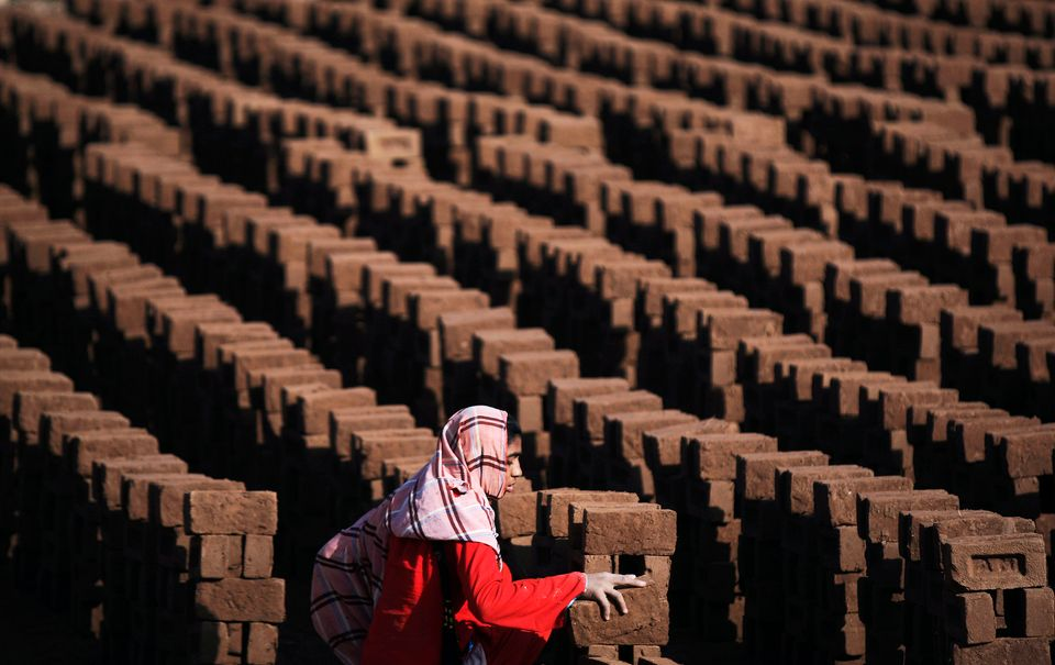 A Pakistani woman arranges bricks as she works at a brick factory on the outskirts of Islamabad, Pakistan, Monday, March 8, 2
