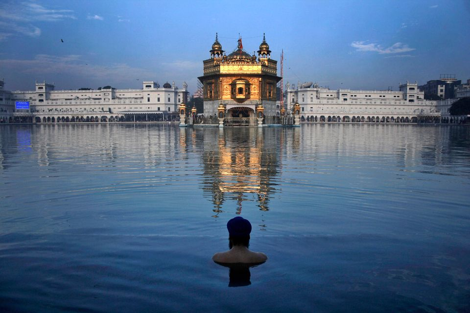 An Indian Sikh devotee takes a holy bath in the sacred pond of the Golden Temple, Sikh's holiest temple, during the birth ann