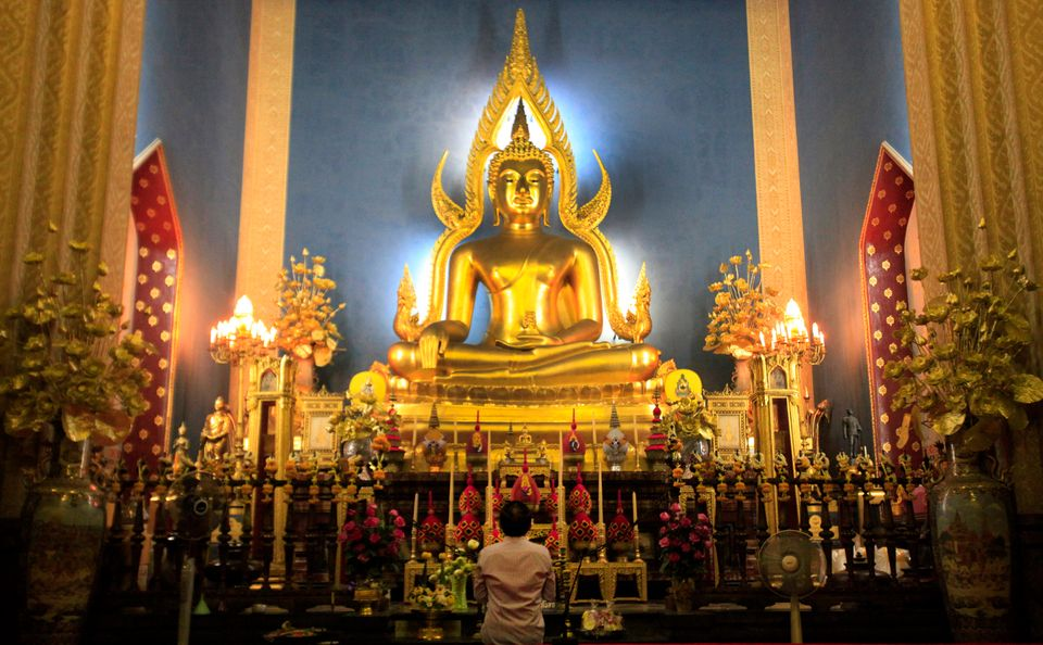A Thai Buddhist prays in front of a giant Buddha statue at Marble temple in Bangkok, Thailand Monday, Jan. 2, 2012.(AP Photo/