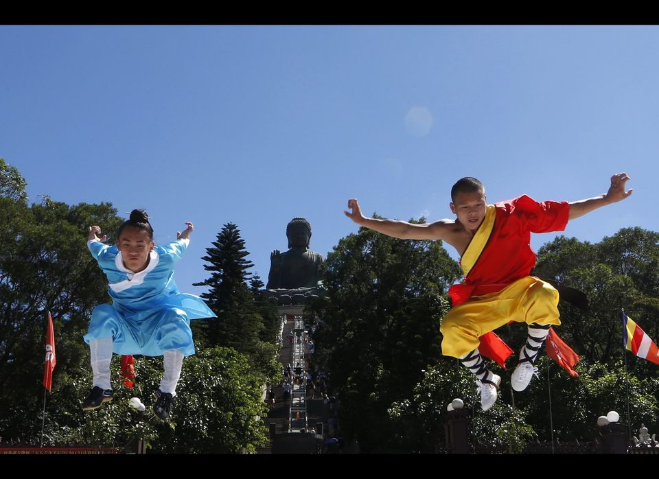 Mainland Chinese kung fu masters Zhang Yong, left and Liu Xin pose in front of the Tian Tan Buddha after performing in the Sh