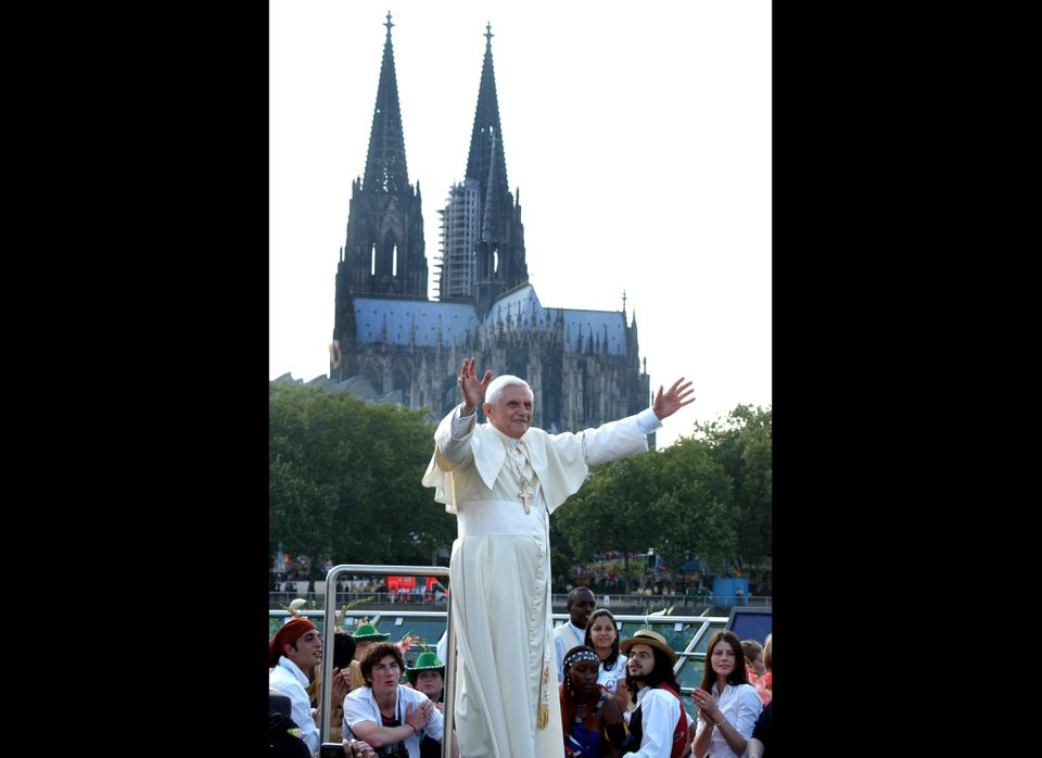 Pope Benedict XVI gestures on the boat in front of the Cologne Cathedral during his trip on Rhein River on August 18, 2005 in