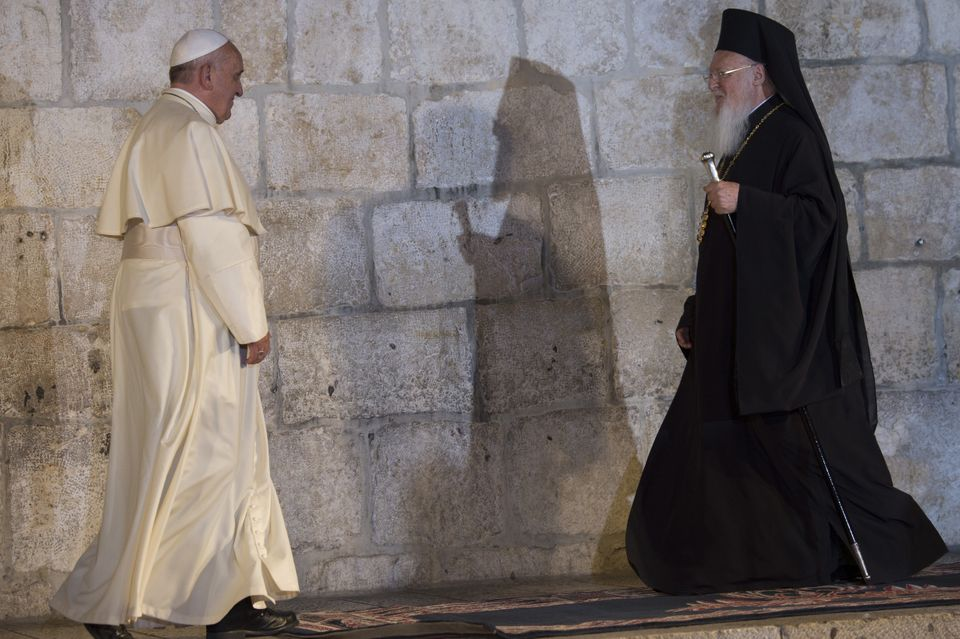 Pope Francis (L) walks towards Ecumenical Patriarch of Constantinople Bartholomew I outside the Church of the Holy Sepulchre