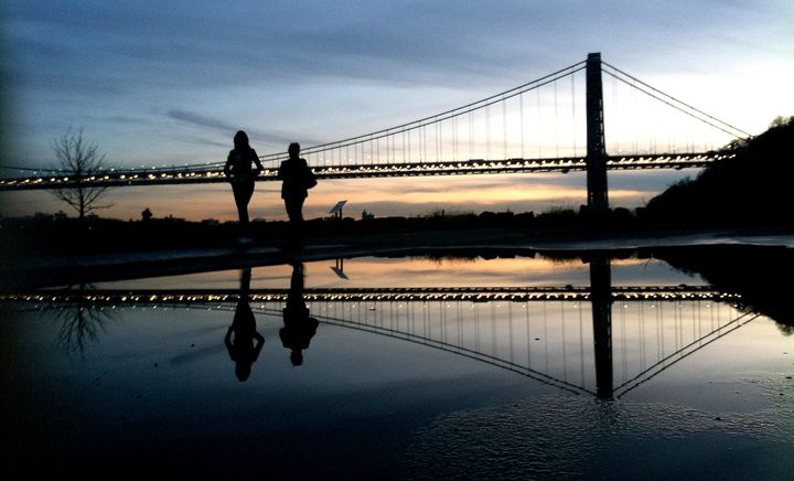 FILE - In this Nov. 26, 2011 file photo two women walk at Palisades Interstate Park as the sun sets over the George Washingto