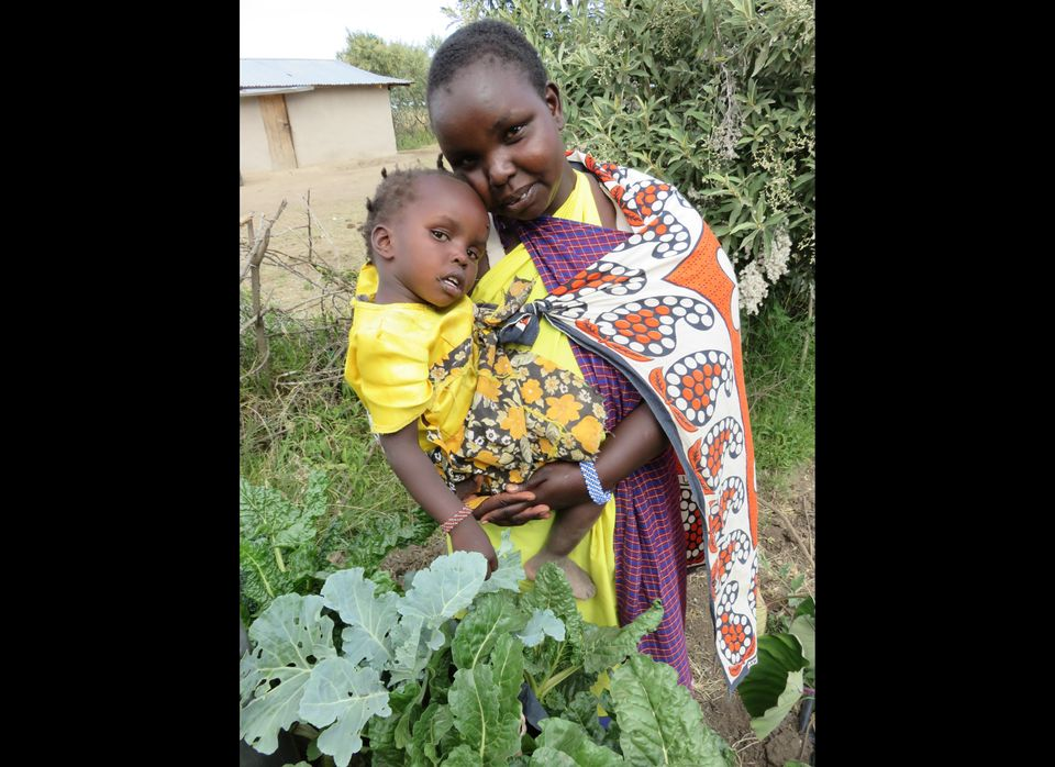 Natana Kisemei holds her youngest daughter, Sein, whose future looks brighter thanks to her mother's education in farming tec