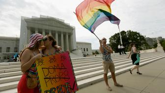 WASHINGTON, DC - JUNE 24:  Gay rights activists Meghan Cleary (L) and Sarah Beth Alcabes from Berkley, CA kiss front of the U.S. Supreme Court building as Vin Testa of DC waves a flag June 24, 2013 in Washington DC. The high court is expected to rule this week on some high profile decisions including California's Proposition 8, the controversial ballot initiative that defines marriage as between a man and a woman.  (Photo by Win McNamee/Getty Images)