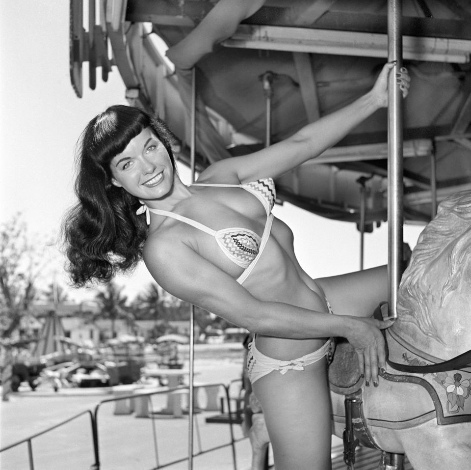 In this photo taken in 1954 by photographer Bunny Yeager, model Bettie Page poses on a merry-go-round at an amusement park in