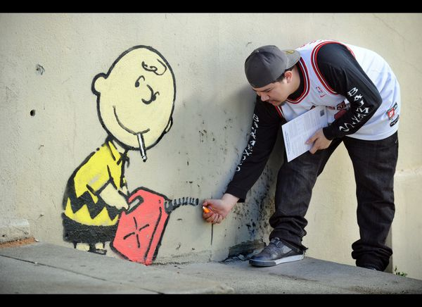 A graffiti attributed to secretive British artist Banksy depicting Charlie Brown figure starting a fire on the side of a burn