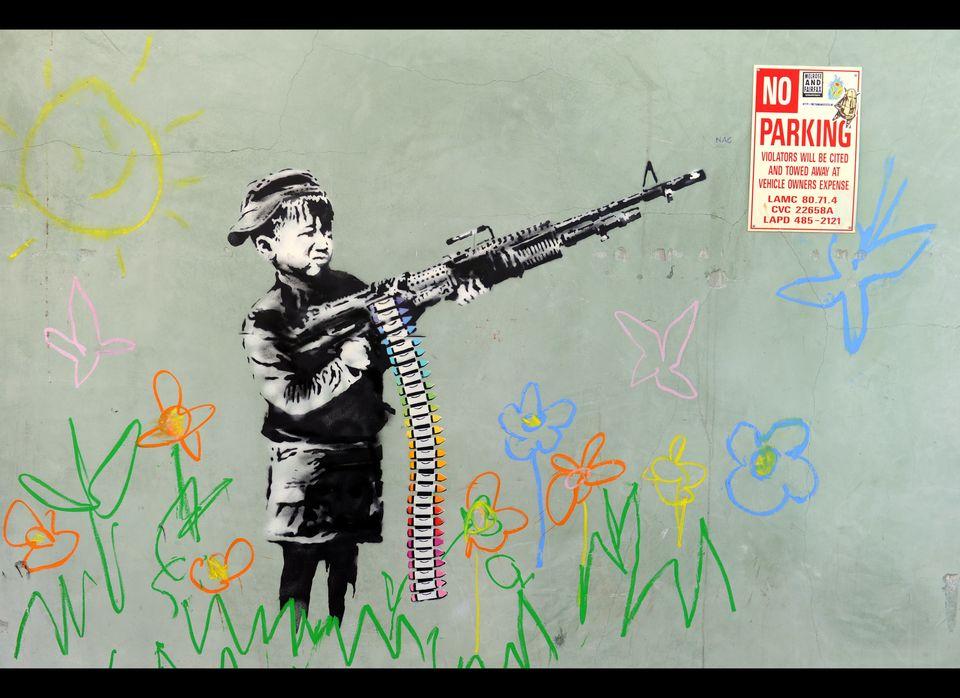 A graffiti attributed to secretive British artist Banksy depicting a child wielding a machine gun, in black and white surroun