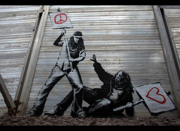 GLASTONBURY, ENGLAND - JUNE 24:  Art work said to be by underground artist Banksy is seen on the fence at the Glastonbury Fes