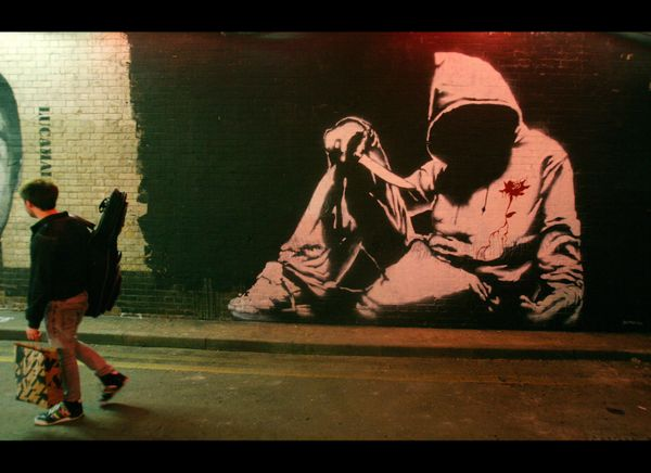 A man walks past a Banksy graffiti artwork during 'Cans' graffiti exhibition in London, on May 3, 2008. British artist Banksy