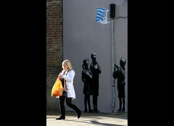 LONDON - MARCH 04:  A lady with a shopping bag passes a recent Banksy work on a wall on March 5, 2008 in London, England. The