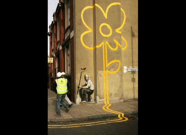 LONDON - NOVEMBER 01:  Builders walk past a new example of 'art' by self styled guerilla artist Banksy on Pollard Street on N