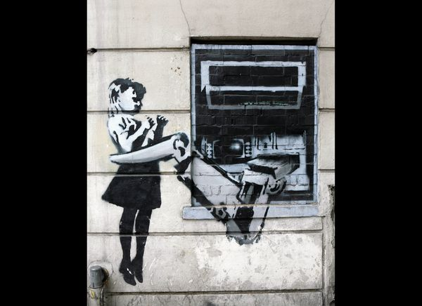 LONDON - MAY 18:  A spray painted depiction of a cash machine grabbing a child adorns a wall in Exmouth Market on May 18, 200