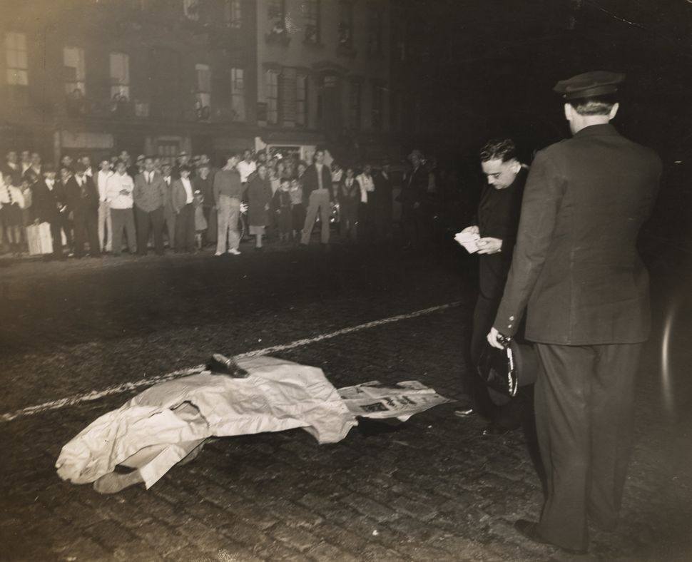 A dead body lies on a cobblestone street covered by paper, newspaper and a shoe; police officer and perhaps a priest stand ne