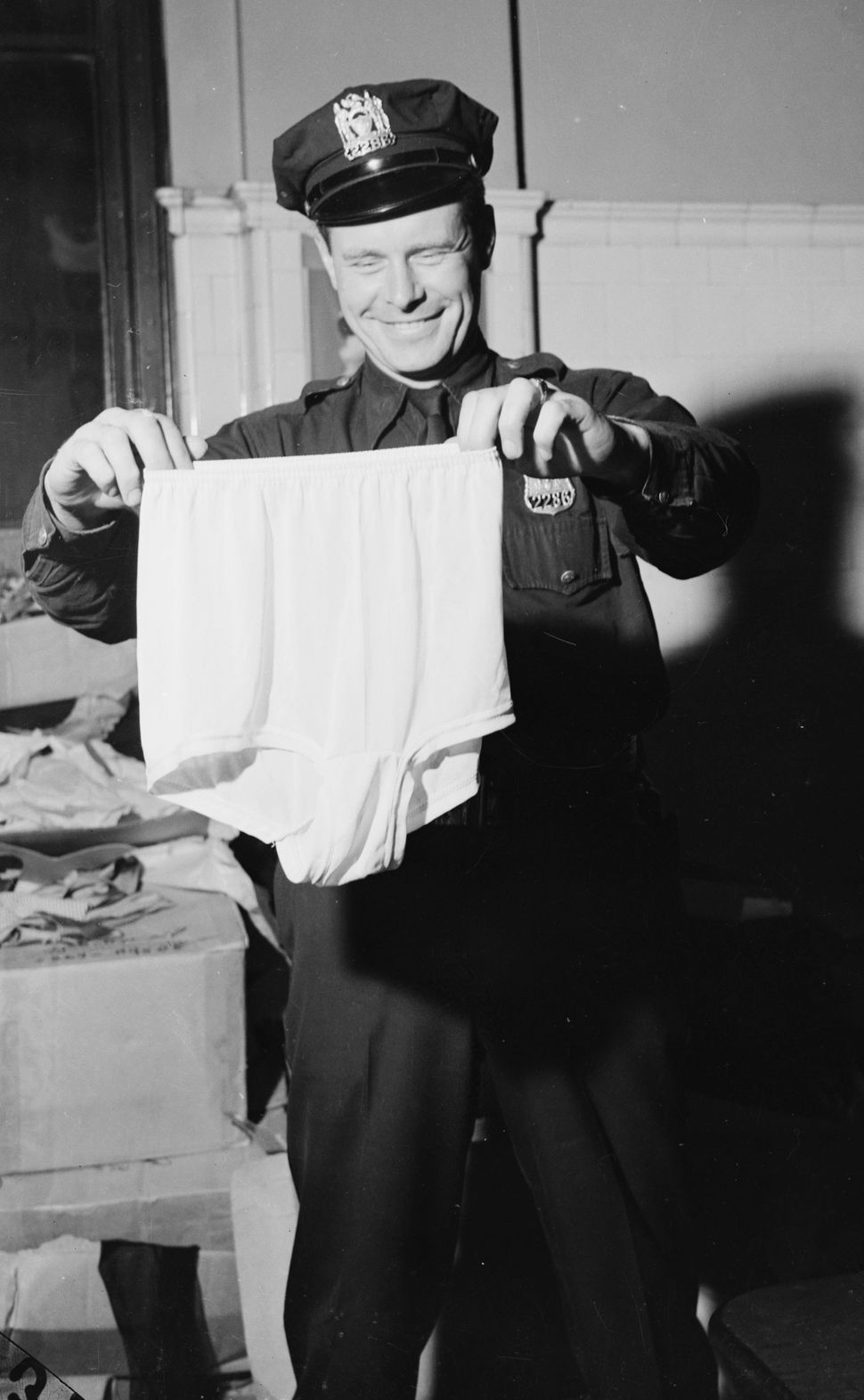 1945: A policeman holds up a large pair of knickers, found amongst some recovered stolen goods in New York.  (Photo by Weegee