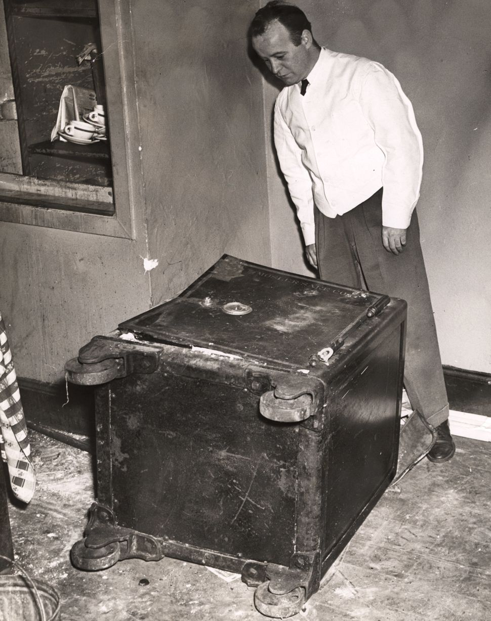 A man looks at a damaged safe, 'The Mosler Safe Co.' printed on the top of the safe, lying on its side; dumb waiter in the ba