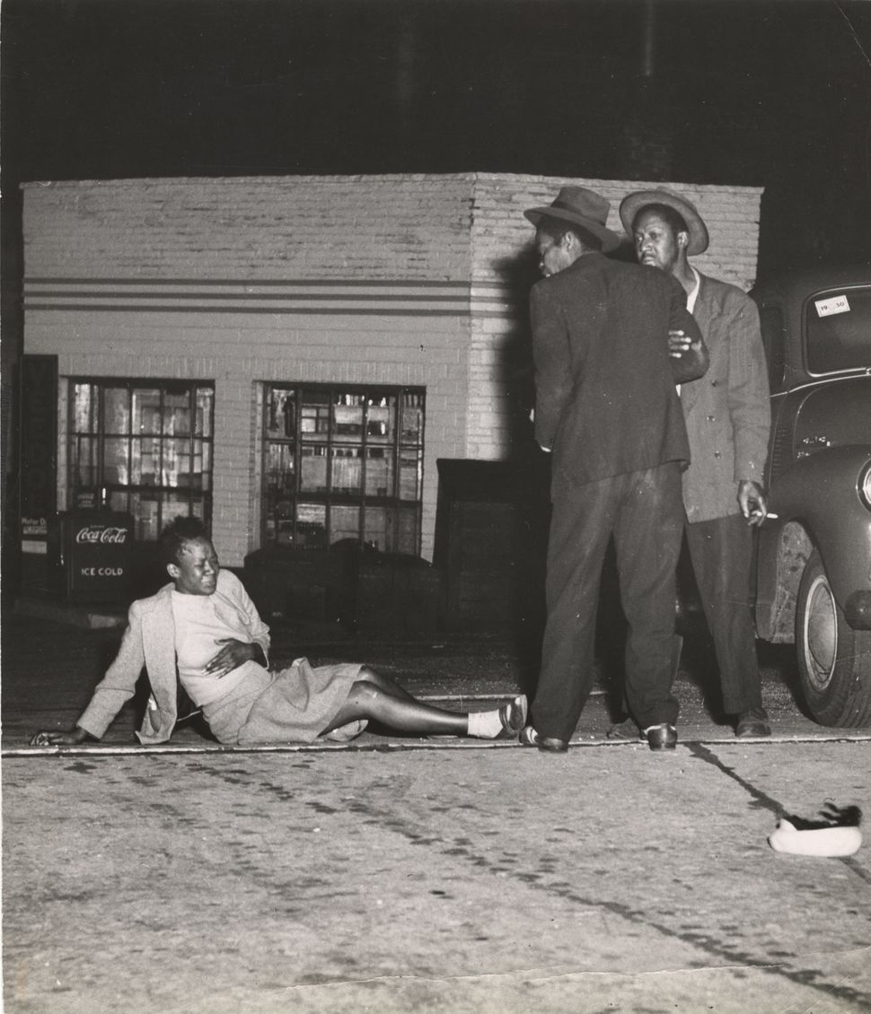 A woman grimaces while clutching her stomach, while on the ground; two men stand above her, on the street at night, New York,