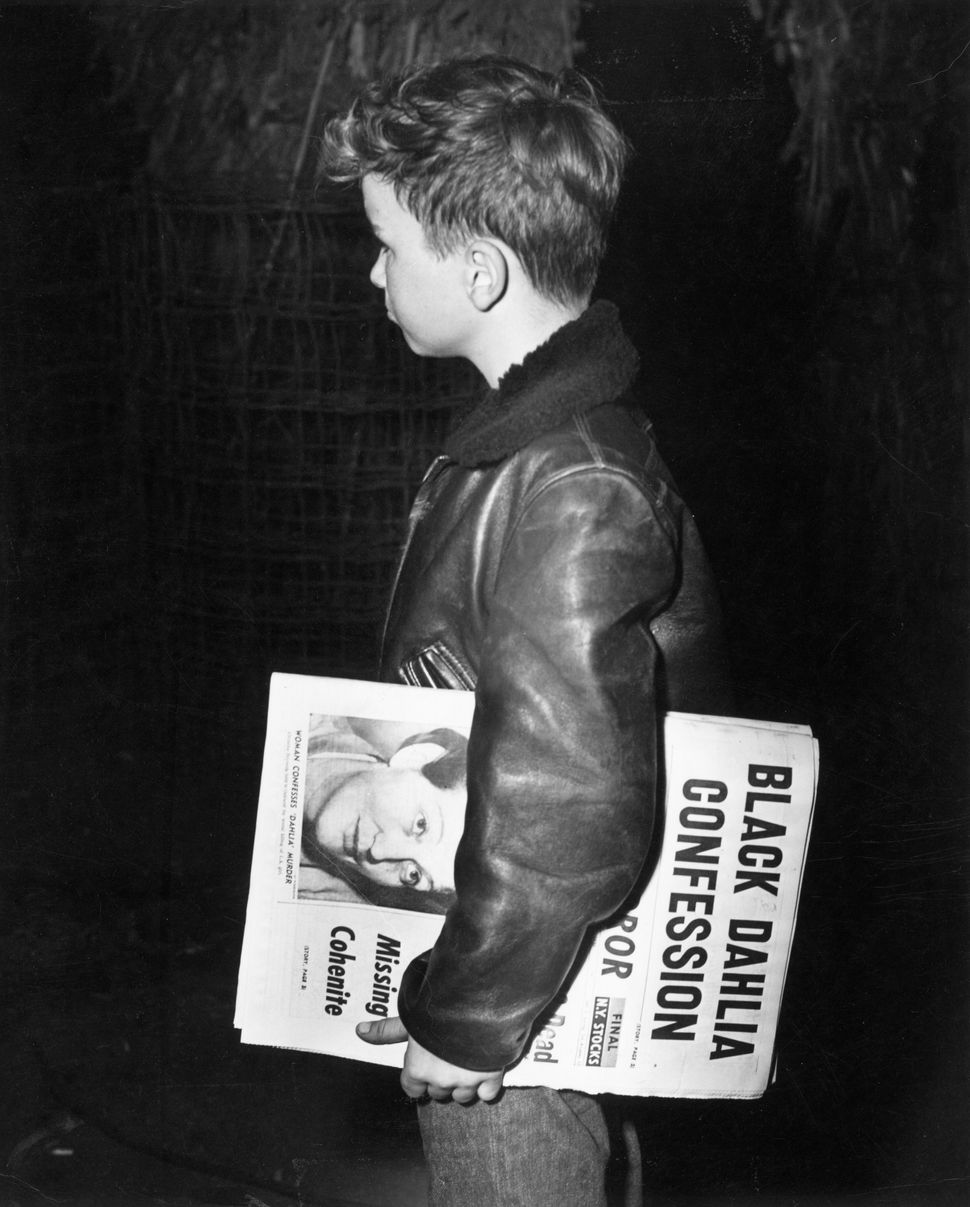 circa 1947:  A newspaper boy in New York City, carrying an edition with the headline 'Black Dahlia Confession'. The headline