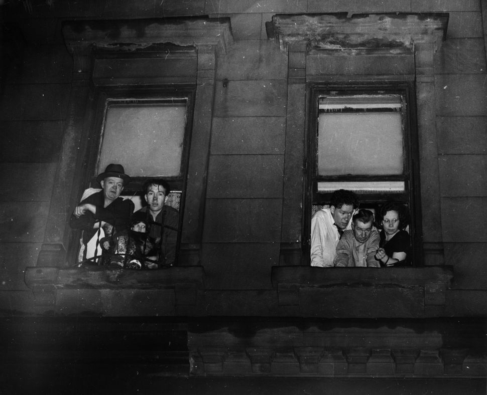 People gather at their windows to look at a murder investigation on the street below in Hell's Kitchen circa 1955 in New York