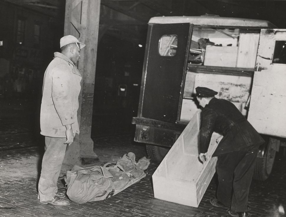 The body of Ruth Fagin Bodenheim is wrapped up in blankets lying on the cobblestone street; two men are about to put it into