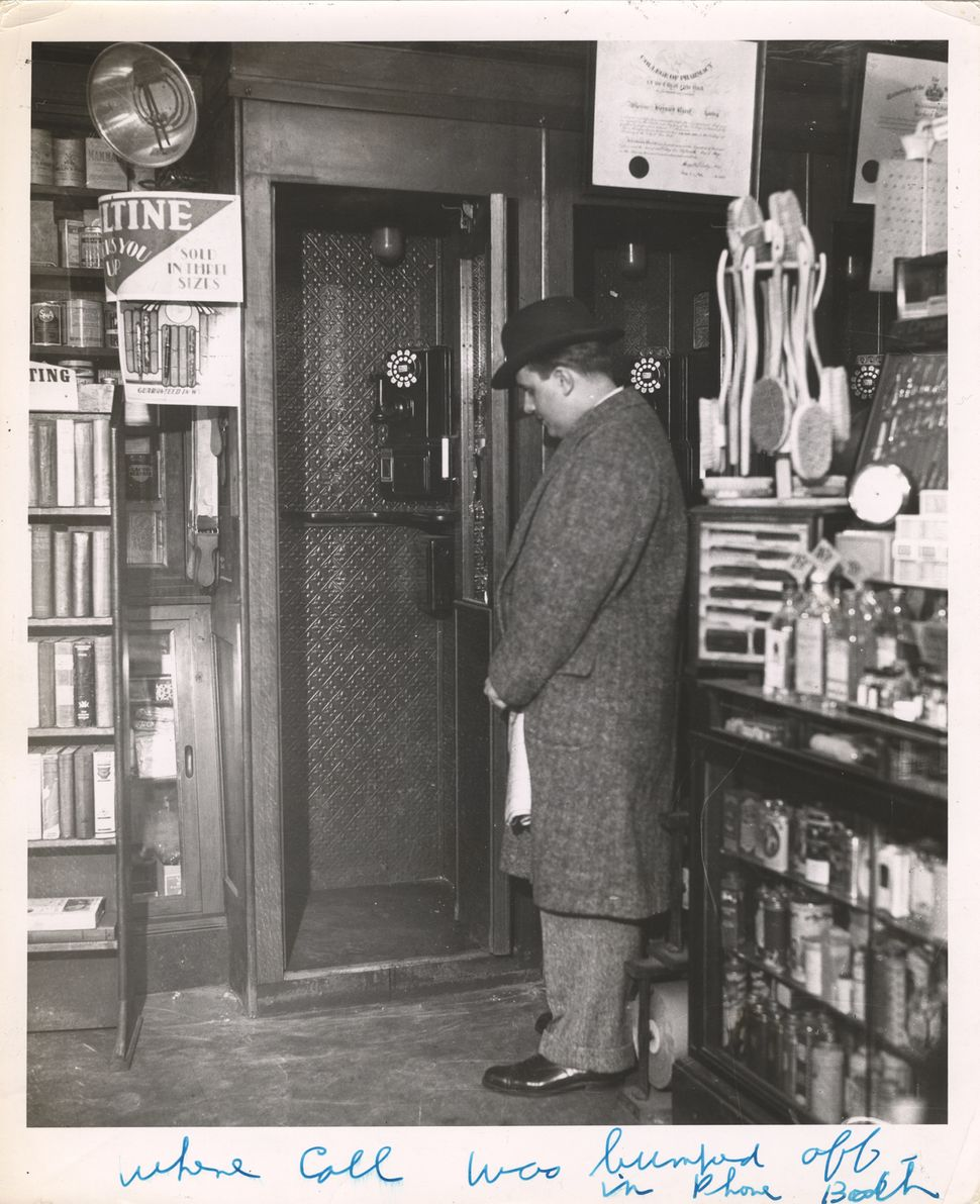 An unidentified man stands beside of a phone booth in the London Chemists drugstore (near the near 23rd Street and Eighth Ave