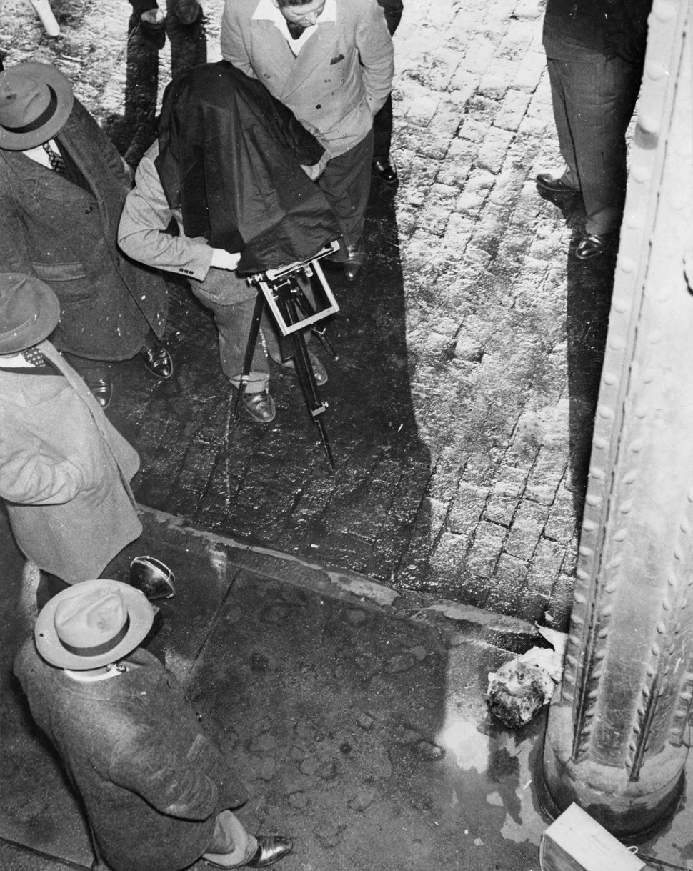circa 1945:  Polish born American photographer Weegee (1899 - 1969) photographs a human head at the scene of a murder.  (Phot