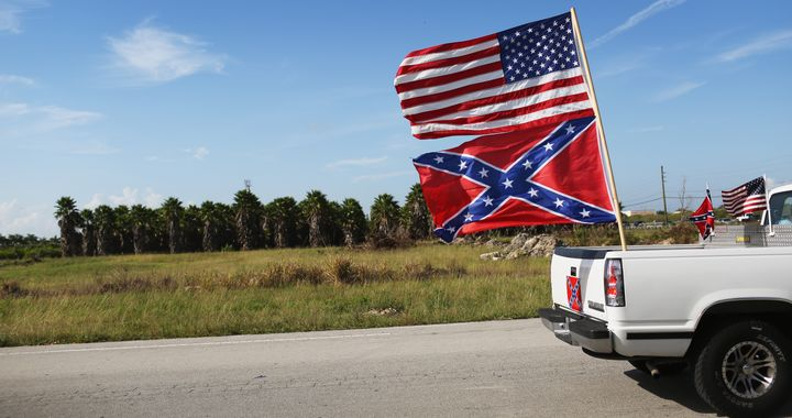 LOXAHATCHEE, FL - JULY 11:  An American and Confederate flag fly from a vehicle during a rally to show support for the flags