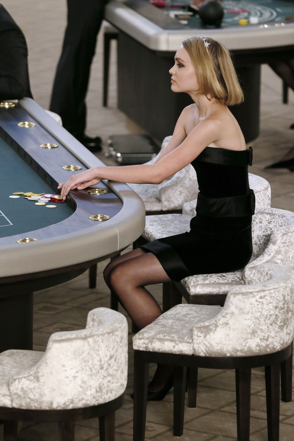 Lily-Rose Depp sits at a casino table during the Chanel 2015-2016 fall/winter Haute Couture collection fashion show on July 7