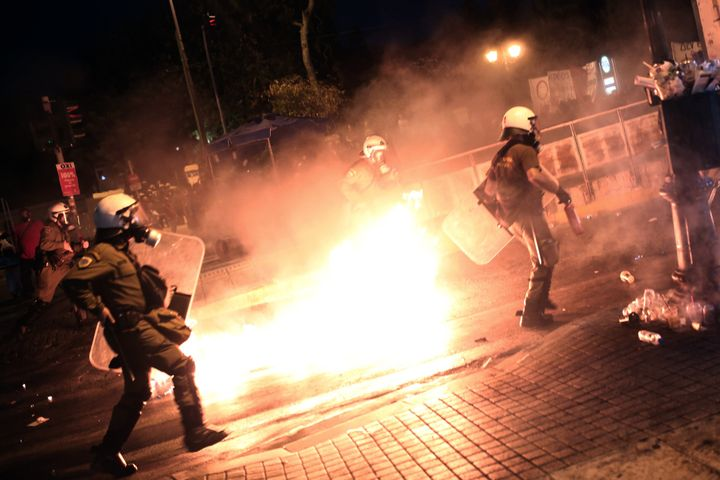 Riot policemen run after protesters throwing petrol bombs in central Athens, during an anti-austerity protest on July 15, 201