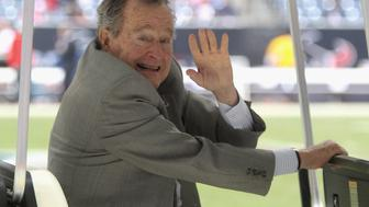 HOUSTON, TX - DECEMBER 01:  Former U.S. President George H.W. Bush waves during the game between the New England Patriots and the Houston Texans at Reliant Stadium on December 1, 2013 in Houston, Texas.  (Photo by Bob Levey/Getty Images)