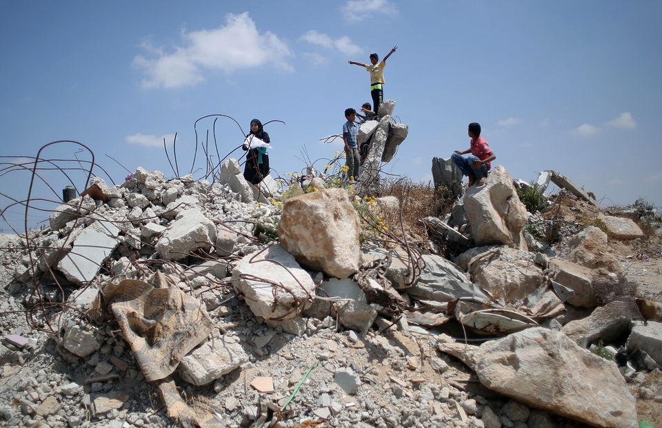 Palestinian children play in the rubble of houses in the village of Khuzaa, Gaza, on July 7, 2015.