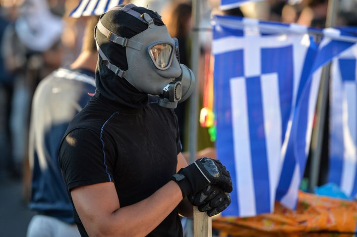 A protester wearing a gas mask attends an anti-austerity protest outside the Greek parliament in Athens on July 15, 2015. Gre