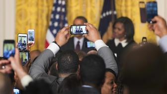 Members of the audience hold up cell phone cameras as US President Barack Obama (C) and First Lady Michelle Obama (R) speak during a reception celebrating Black History Month at the White House in Washington, DC, on February 26, 2015.    AFP PHOTO/JIM WATSON        (Photo credit should read JIM WATSON/AFP/Getty Images)