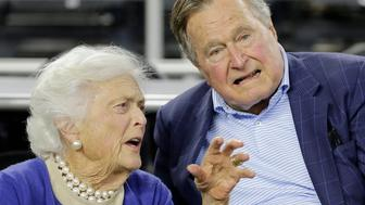 FILE- In this March 29, 2015, photo, former President George H.W. Bush and his wife Barbara Bush speak before the first half of a college basketball game in Houston. The former first lady is promoting literacy on her 90th birthday by lending her backing to a $7 million challenge by X Prize and Dollar General. Theyre challenging developers to create a mobile app to help improve adult literacy skills. (AP Photo/David J. Phillip, File)