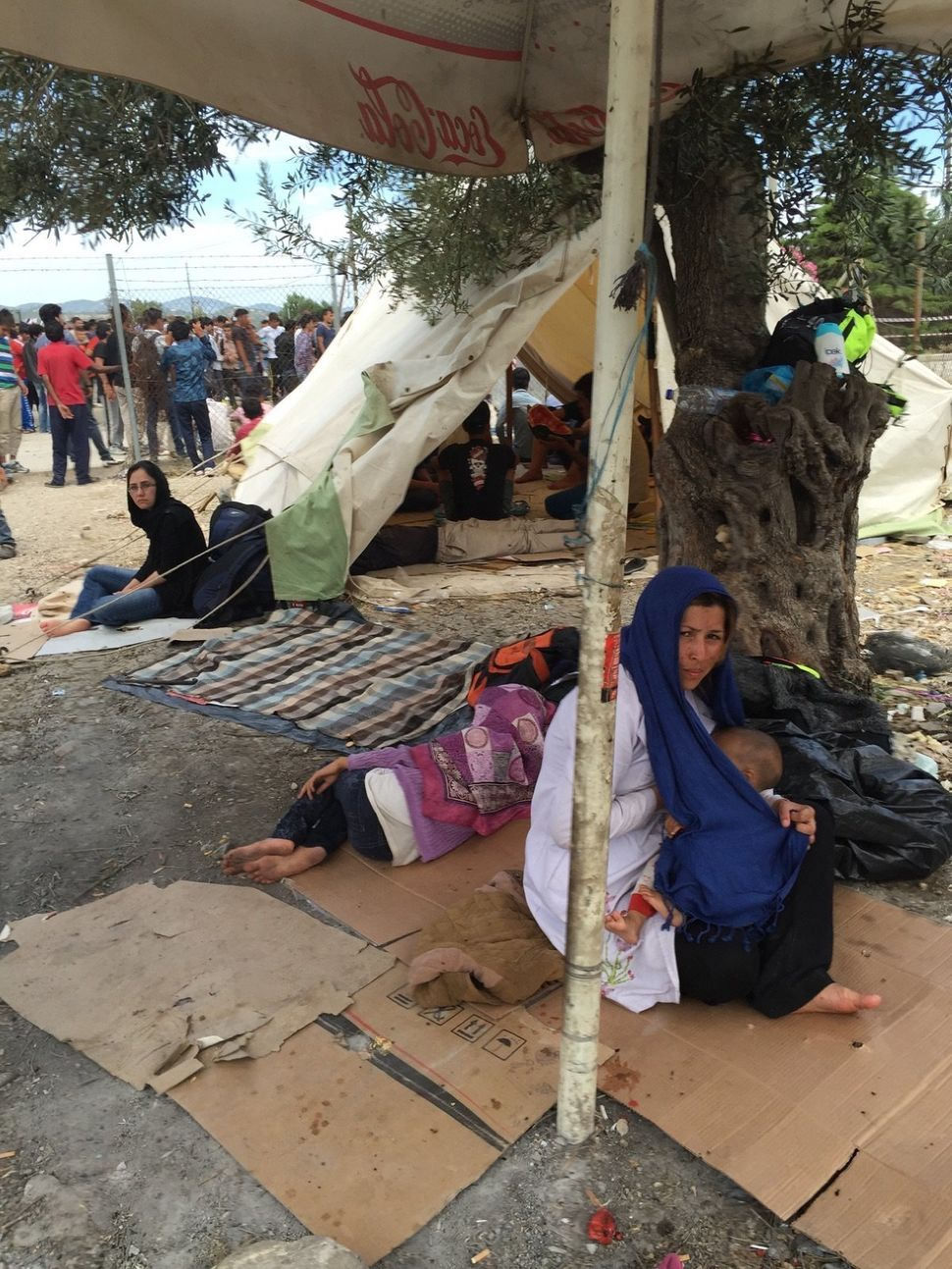 Migrants rest in the shade in Kara Tepe camp in Lesbos, Greece.