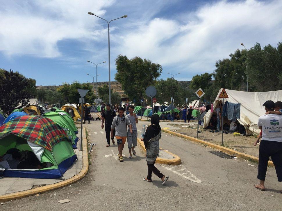 Migrants walk bytheir tents in Kara Tepe camp in Lesbos, Greece.