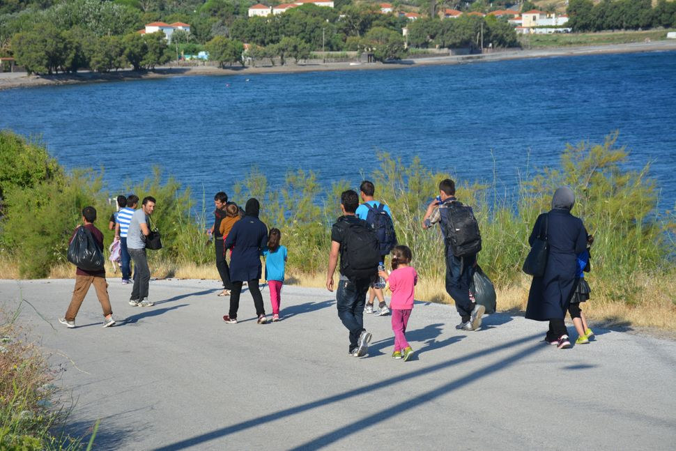 Migrantstravel 40 miles by foot upon arrival to the nearest transit camps in Lesbos, Greece.