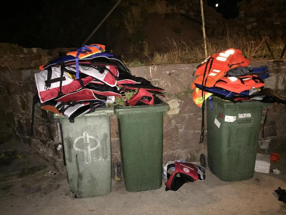 Life jackets left behind by new migrants sit atop garbage bins in Lesbos, Greece.