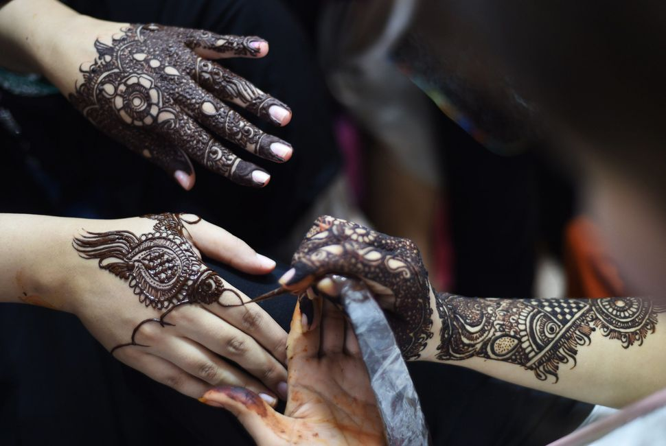Pakistani beauticians apply henna designs to customers ahead of the Eid al-Fitr holiday which marks the end of Ramadan at a b
