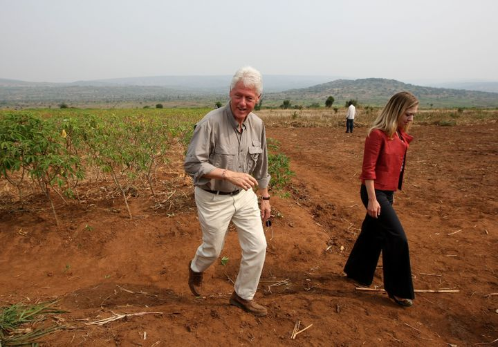 RWINKWAVU, RWANDA - AUGUST 02:  Former U.S. President Bill Clinton (L) and his daughter Chelsea visit a cassava farm August 2