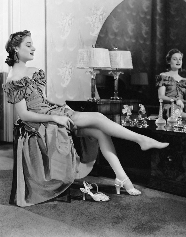 UNITED STATES - CIRCA 1950s:  Woman at dressing table putting on stockings.  (Photo by George Marks/Retrofile/Getty Images)